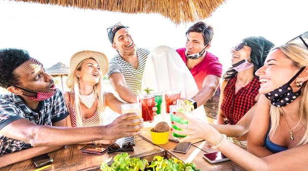 Junge gemischtrassige freunde, die an strandcocktailkneipe mit offener gesichtsmaske trinken