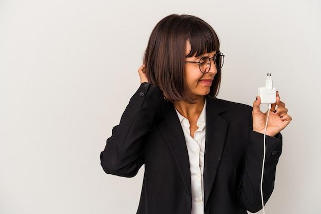 Junge gemischtrassige geschäftsfrau, die ein telefonladegerät lokalisiert auf weißem hintergrund hält und seitlich mit zweifelhaftem und skeptischem ausdruck schaut.