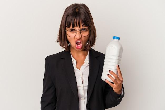 Junge gemischtrassige geschäftsfrau, die eine milchflasche lokalisiert auf weißem hintergrund hält, die sehr wütend und aggressiv schreit.