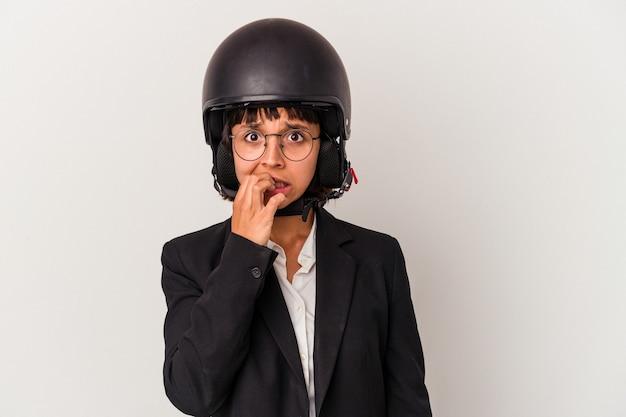 Junge gemischtrassige geschäftsfrau, die einen motorradhelm trägt, isoliert beißende fingernägel, nervös und sehr ängstlich.