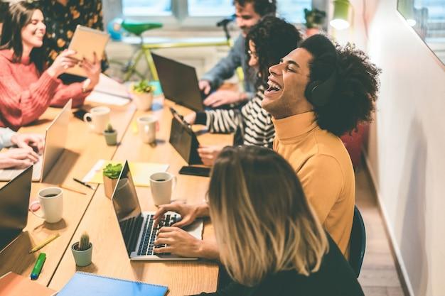 Junge gemischtrassige menschen, die spaß an der arbeit im coworking-büro haben - focus african man face