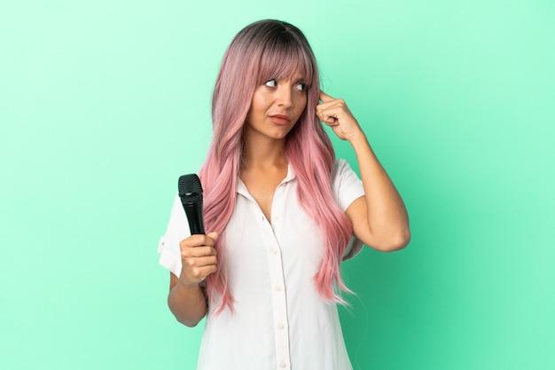 Junge gemischtrassige sängerin mit rosa haaren isoliert auf grünem hintergrund, die zweifel hat und denkt