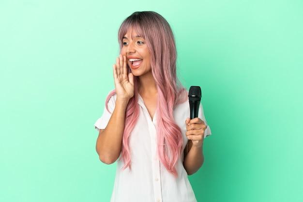 Junge gemischtrassige sängerin mit rosa haaren isoliert auf grünem hintergrund schreien mit weit geöffnetem mund zur seite