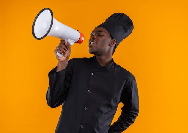 Junge genervte afroamerikanische köchin in kochuniform schreit durch lautsprecher auf orange mit kopierraum
