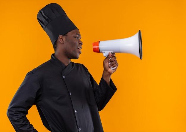 Junge genervte afroamerikanische köchin in kochuniform steht seitlich und spricht durch lautsprecher auf orange mit kopierraum