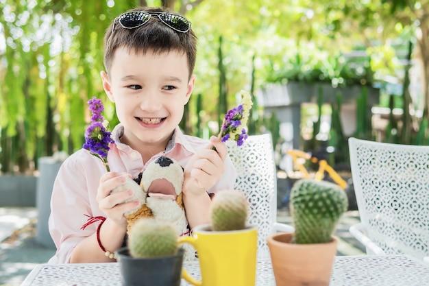 Junge genießen, mit blume und kaktus in einem restaurant zu spielen - der junge, der mit naturkonzept glücklich ist