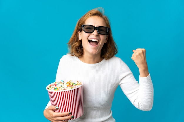 Junge georgianische frau lokalisiert mit 3d-brille und hält einen großen eimer popcorn