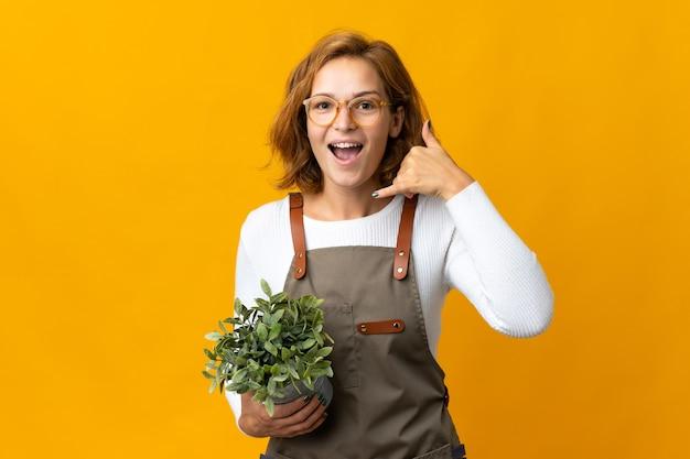 Junge georgische frau, die eine pflanze lokalisiert auf gelber wand hält, die telefongeste macht. rufen sie mich zurück zeichen
