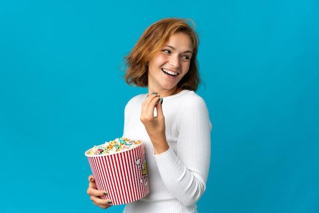 Junge georgische frau isoliert, die einen großen eimer popcorn hält