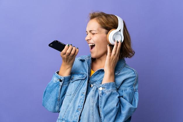 Junge georgische frau lokalisiert auf lila hintergrund, der musik mit einem handy und gesang hört
