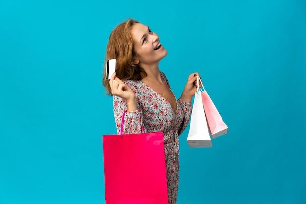 Junge georgische frau mit einkaufstasche lokalisiert auf blauem hintergrund, der einkaufstaschen und eine kreditkarte hält