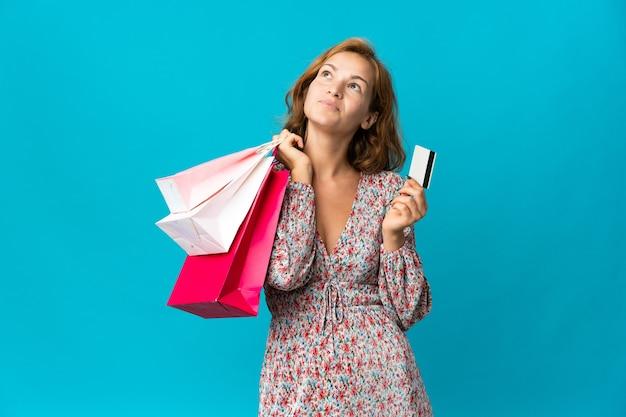 Junge georgische frau mit einkaufstasche lokalisiert auf blauem hintergrund, der einkaufstaschen und eine kreditkarte und das denken hält