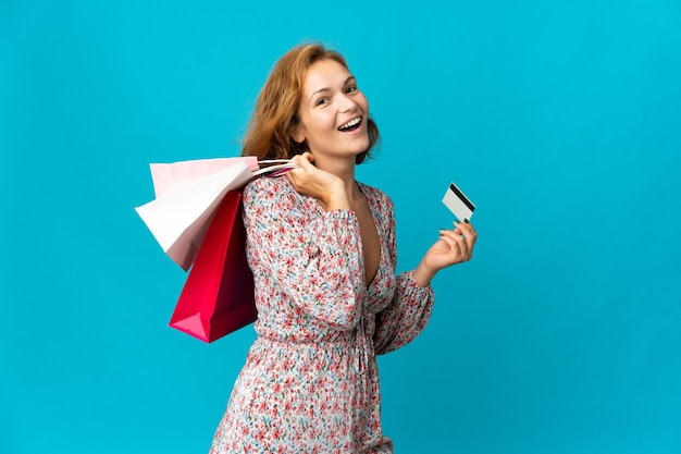 Junge georgische frau mit einkaufstasche lokalisiert auf blauer wand, die einkaufstaschen und eine kreditkarte hält