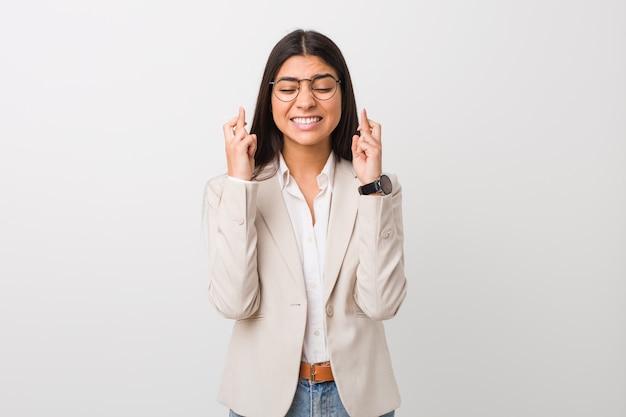 Junge geschäftsaraberfrau lokalisiert gegen finger einer weiße wandüberfahrt für das haben des glücks