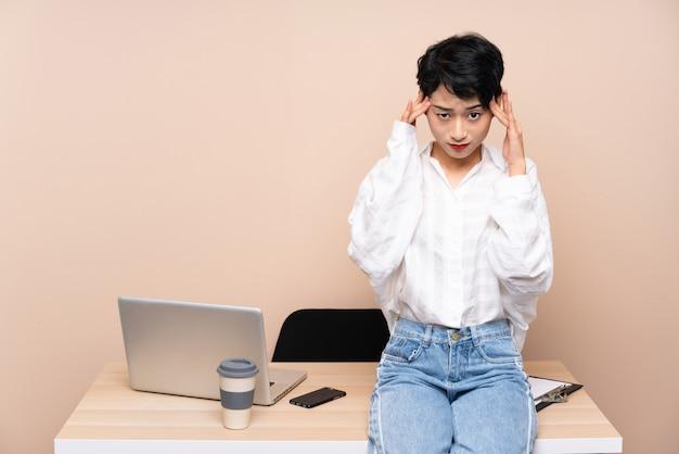 Junge geschäftsasiatin an ihrem arbeitsplatz unglücklich und frustriert mit etwas. negativer gesichtsausdruck