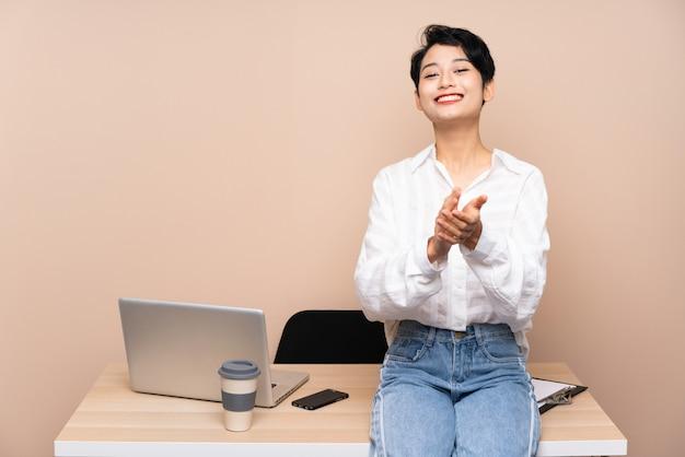 Junge geschäftsasiatin in ihrem arbeitsplatz applaudiert