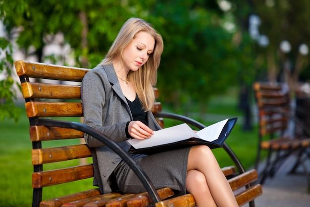 Junge geschäftsdame, die auf bank sitzt und dokumente liest