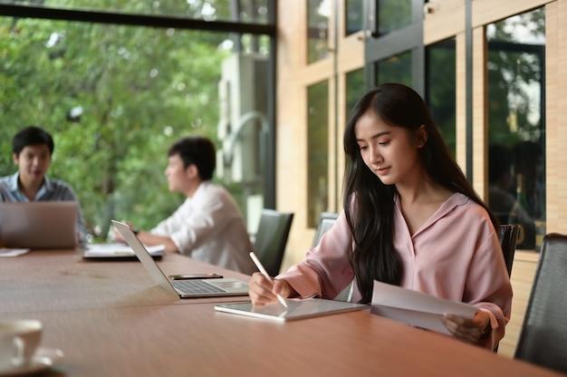 Junge geschäftsfrau am modernen startup-büro, das auf tablette arbeitet, verwischte team im besprechungshintergrund.