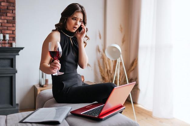 Junge geschäftsfrau arbeiten zu hause. auf dem tisch sitzen und telefonieren. halten sie ein glas rotwein in der hand. brünettes model trägt ein schwarzes kleid und einen braunen schal.