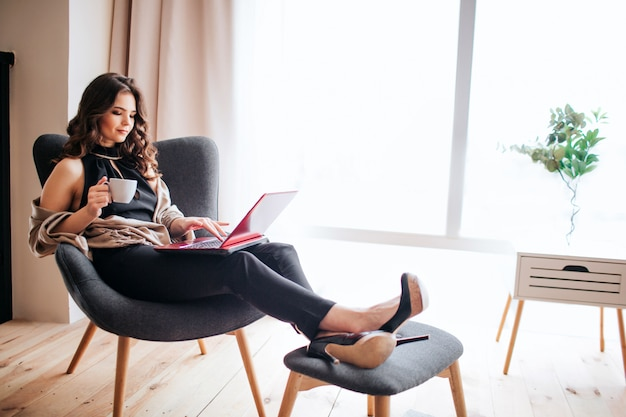 Junge geschäftsfrau arbeiten zu hause. kaffee trinken und lernen. füße auf kleinem stuhl halten. tippen auf einem tastatur-laptop. konzentriertes beschäftigtes modell. allein im zimmer.