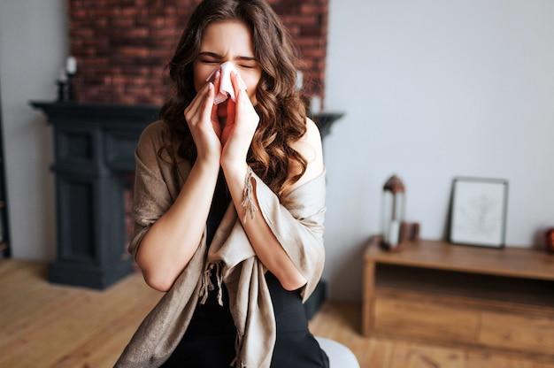 Junge geschäftsfrau arbeiten zu hause. krankes modell erkältet und virus. nase mit taschentuch abdecken. allein im zimmer. leiden sie an grippe oder virus.