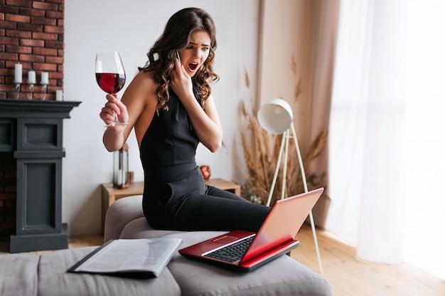 Junge geschäftsfrau arbeiten zu hause. telefonieren und auf tisch im wohnzimmer sitzen. schauen sie auf lpatop und halten sie ein glas mit rotwein in der hand. schöne brünette, die hart arbeitet.