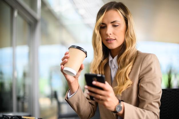 Junge geschäftsfrau auf einer kaffeepause mit ihrem smartphone