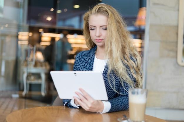 Junge geschäftsfrau auf einer kaffeepause. tablettcomputer verwenden.