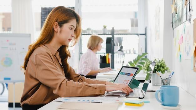 Junge geschäftsfrau aus asien, die soziale distanzierung in einer neuen normalen situation zur virenprävention hält, während sie laptop und tablet wieder bei der arbeit im büro verwendet