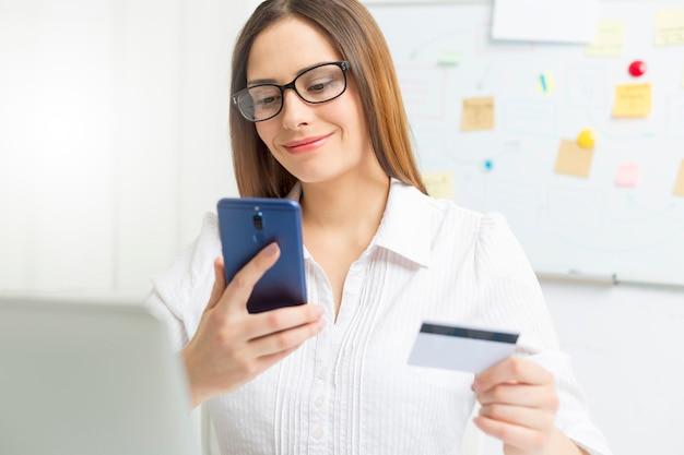 Junge geschäftsfrau benutzt einen handy und eine kreditkarte für online-zahlung.