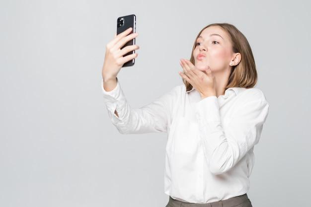Junge geschäftsfrau blasen kuss, während selfie am telefon lokalisiert auf weißer wand nehmen