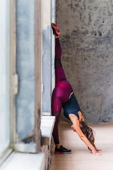 Junge geschäftsfrau der eignung, die nahe dem übenden yoga des fensters sich lehnt