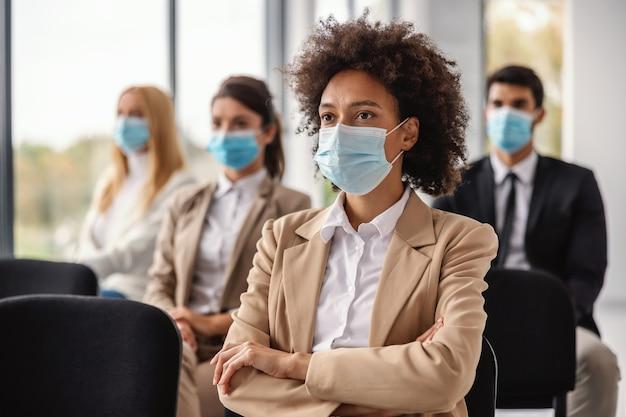 Junge geschäftsfrau der gemischten rasse, die auf seminar sitzt und präsentation während des ausbruchs des koronavirus hört.