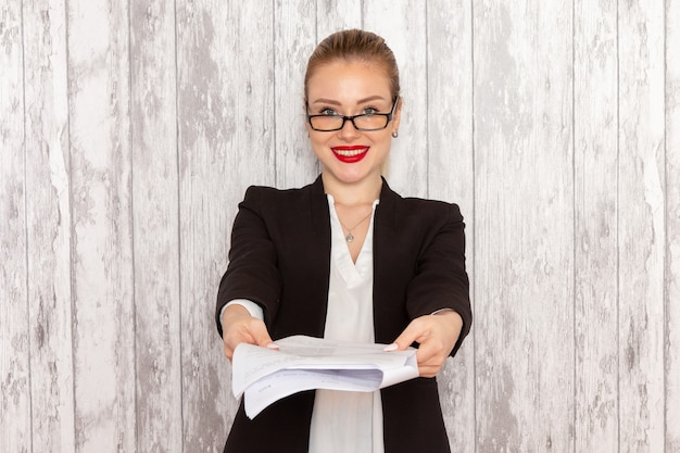 Junge geschäftsfrau der vorderansicht in der schwarzen jacke der strengen kleidung, die dokument lächelnd auf weißer oberfläche gibt
