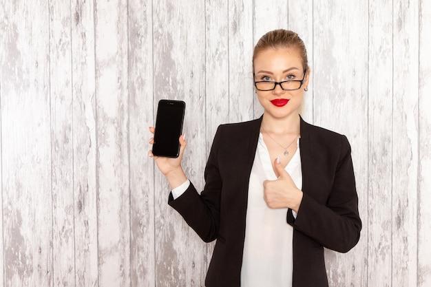 Junge geschäftsfrau der vorderansicht in der schwarzen jacke der strengen kleidung, die ihr smartphone auf weißer oberfläche hält