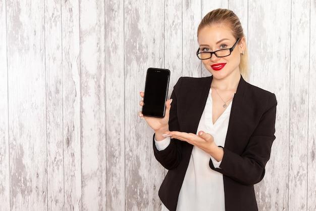Junge geschäftsfrau der vorderansicht in der schwarzen jacke der strengen kleidung, die ihr telefon auf weißem schreibtisch hält