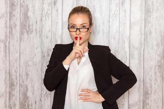 Junge geschäftsfrau der vorderansicht in der schwarzen jacke der strengen kleidung mit optischer sonnenbrille, die auf weiblichem geschäft des grauweißen wandarbeitsarbeitsbüros aufwirft
