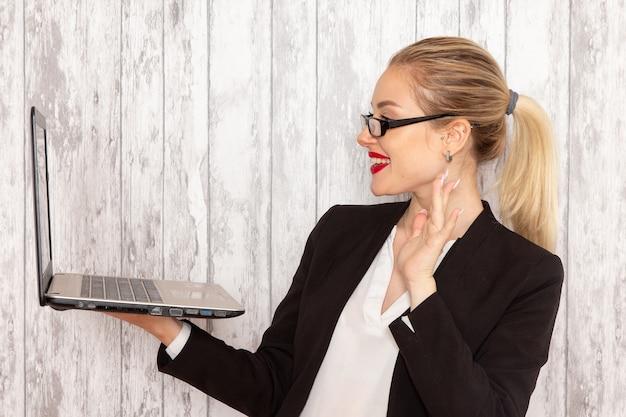 Junge geschäftsfrau der vorderansicht in der schwarzen jacke der strengen kleidung unter verwendung ihres laptops, der auf weißer oberfläche lächelt