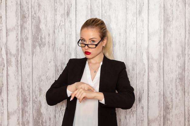 Junge geschäftsfrau der vorderansicht in der strengen schwarzen jacke der kleidung mit optischer sonnenbrille, die ihr handgelenk auf weiblichem geschäft des weißen wandarbeitsarbeitsbüros zeigt