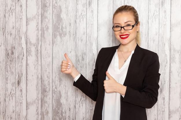 Junge geschäftsfrau der vorderansicht in strikter schwarzer jacke der kleidung mit optischer sonnenbrille mit lächeln auf weiblichen geschäftstreffen der weißen wandarbeitsstelle