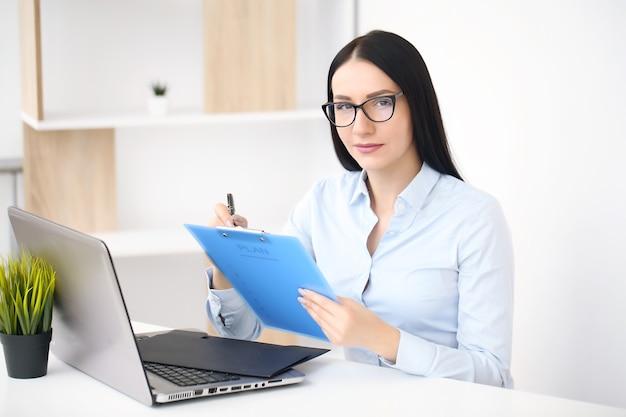 Junge geschäftsfrau des schönen brunette im büro, das ordnerkopienraum zeigt.
