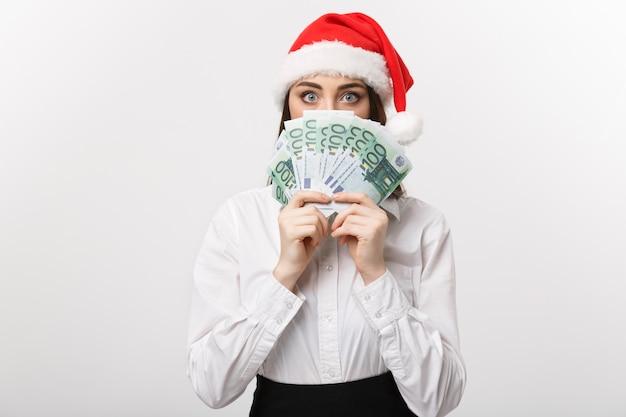 Junge geschäftsfrau des weihnachts- und finanzkonzepts, die geld zeigt, das ihr gesicht mit überraschungsausdruck schließt