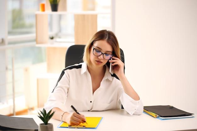 Junge geschäftsfrau, die am arbeitsplatz sitzt und papier im büro liest.