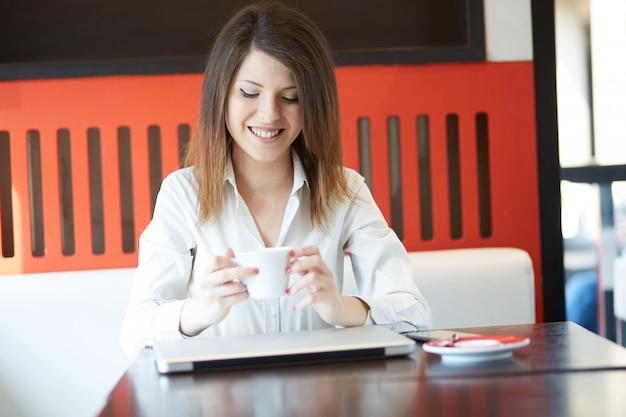 Junge geschäftsfrau, die am café arbeitet
