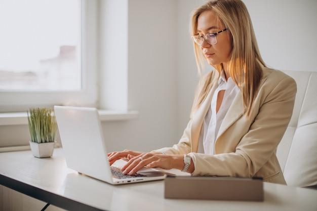 Junge geschäftsfrau, die am computer im büro arbeitet