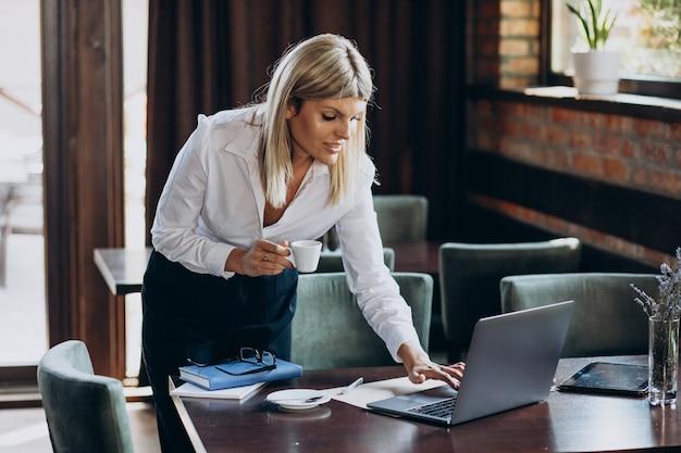 Junge geschäftsfrau, die am computer in einem café arbeitet