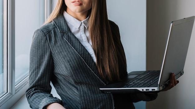 Junge geschäftsfrau, die am fenster mit laptop steht