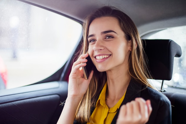 Junge geschäftsfrau, die am handy im auto spricht