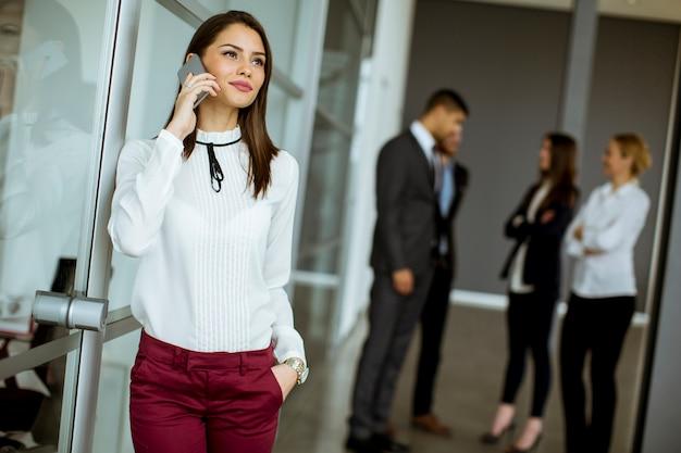 Junge geschäftsfrau, die am handy im büro spricht