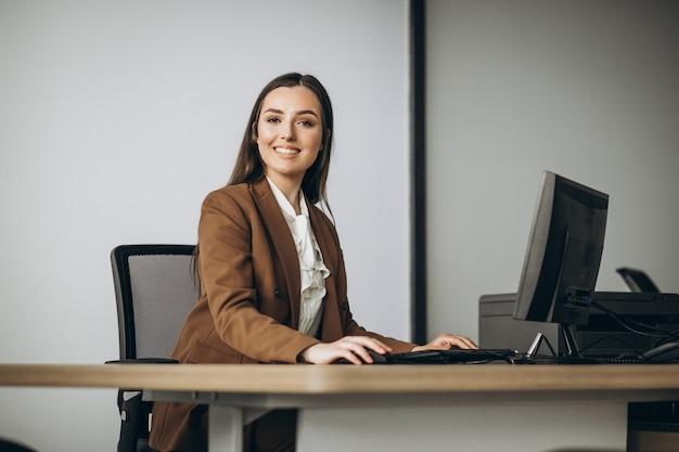 Junge geschäftsfrau, die am laptop im büro arbeitet